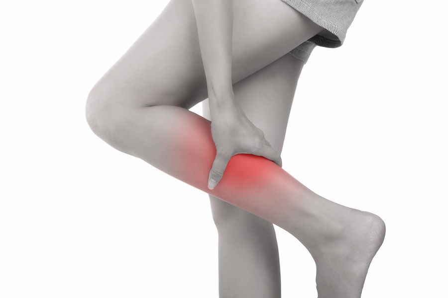 Woman with calf feeling pain on white background